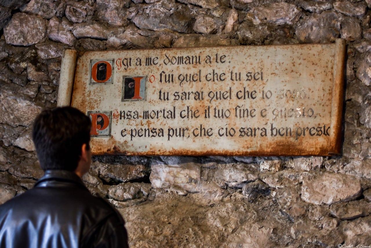 L'iscrizione che accoglie i visitatori all'ingresso della Cripta adibita a Museo delle Mummie di Ferentillo, Umbria